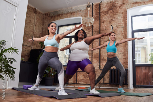 Adorable women exercising at home with pleasure Wallpaper Mural