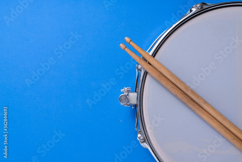 Fototapeta Drum stick and drum on blue table background, top view, music concept obraz