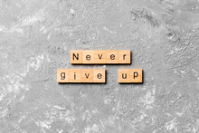 Never Give Up Word Written On Wood Block. Never Give Up Text On Cement Table For Your Desing, Concept