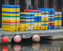 Multi-colored Plastic Fish Crates Or Boxes Stacked On The Quay Beside A Rusty Harbor Wall, Waiting To Be Filled When The Fishing Boats Return From The Sea With Their Catch.