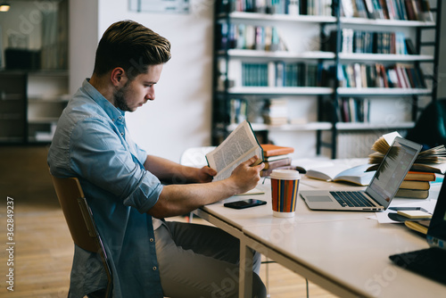 Fototapeta Serious caucasian male student sitting at desktop with book preparing for college examination,clever young man reading textbook spening time on autodidact analyzing literature in university library obraz