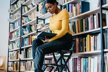 Smart Black Woman Reading Book Near Bookcase