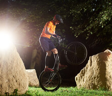 Extreme Cyclist On Bmx Bike In Park Performing Stunt Keeping Balance On Back Wheel, Side View