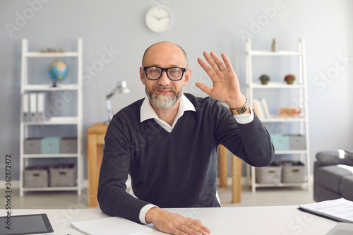 Obraz Waving old businessman smiling looking at the camera video call web camera gadget sitting in the apartment. - fototapety do salonu