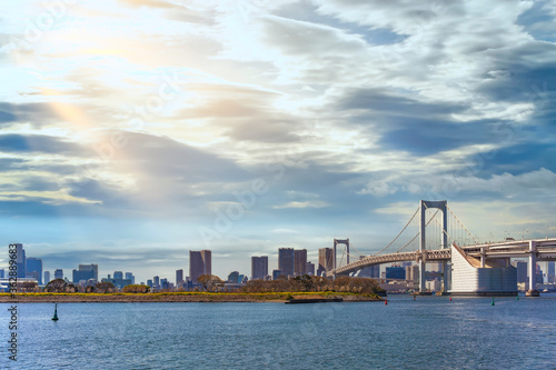 Seascape of the Bird Island of Odaiba Bay in front of the double-layered suspension Rainbow Bridge in the port of Tokyo with altostratus clouds in the sky Canvas Print