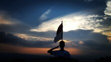 Silhouette Man With Flag Saluting Against Sky During Sunset