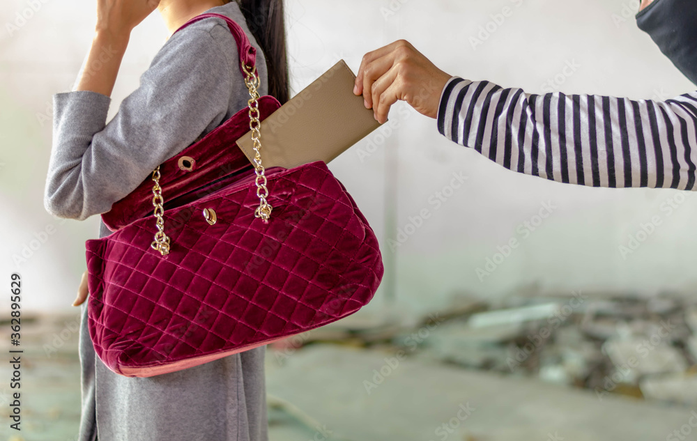 Fototapeta man pickpocketing a purse from woman's bag