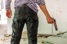 Close Up Back View Of Bandit Catch A Hidden Gun,A Man Holding A Gun In His Hand Behind His Back, Close-up View. Concepts: Crime, Attempted Murder, A Gunshot Wound, The Killer