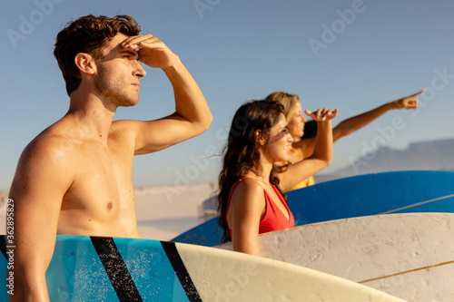 Multi-ethnic group of male and female, surfing on the beach