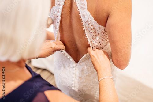 Obraz na płótnie Midsection Of Woman Helping Bride To Dress Up