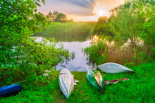 Sunset At River With Kayaks Ly...