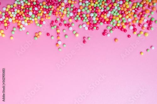 Fototapeta Decorative sugar sprinkles on a pink backdrop. obraz