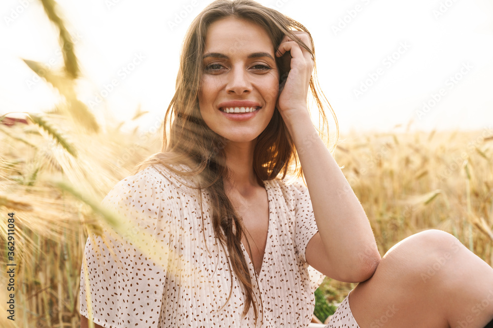 Fototapeta Photo of joyful caucasian woman sitting and smiling while walking