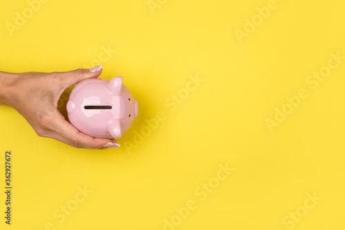 Fototapeta Woman holding a  piggy bank on a yellow desk obraz