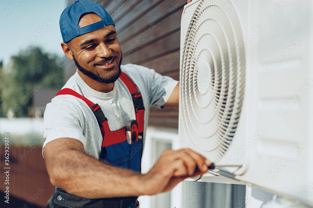 Fototapeta Young black man repairman checking an outside air conditioner unit