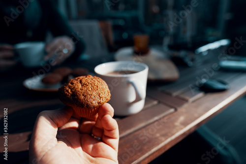 Fotografering Close-up Of Hand Holding Cake On Table