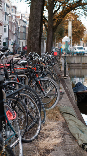 Photo Bicycles parked near a canal in Amsterdam, Netherlands
