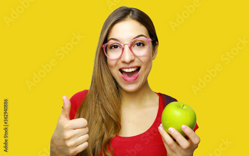 Young Woman Holding Granny Smith Apple Against Yellow Background Poster Mural XXL