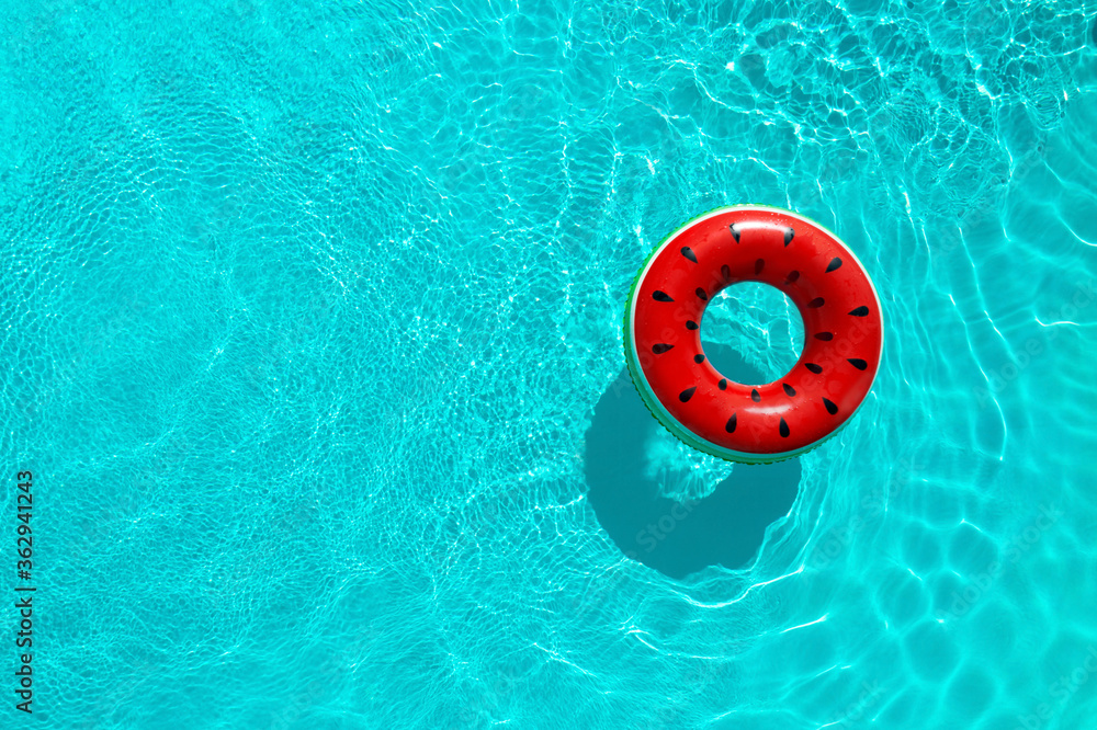Fototapeta Inflatable ring floating in swimming pool, top view with space for text. Summer vacation
