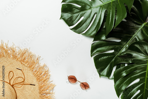 Obraz top view of green palm leaves, straw hat and sunglasses on white background - fototapety do salonu