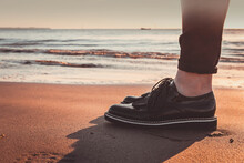 Low Section Of Woman In Shoe Standing At Beach During Sunset