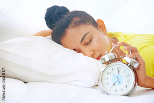 Obraz A sleepy woman lies in bed while picking up an alarm clock in the morning. - fototapety do salonu