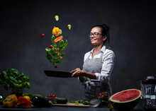 Happy Middle-aged Female Chef Tossing Chopped Vegetables In The Air From A Frying Pan. Healthy Food Concept. Studio Photo On A Dark Background