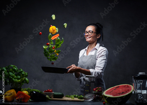 Happy middle-aged female chef tossing chopped vegetables in the air from a frying pan Fototapet