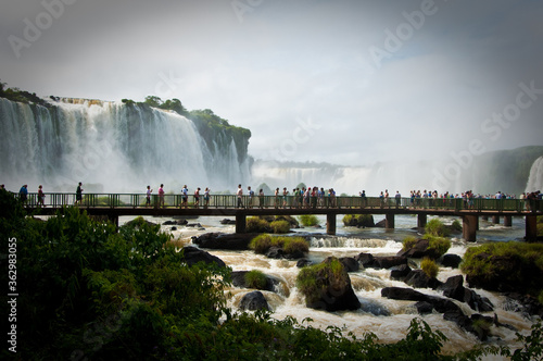 Group Of People On Footbridge Over River By Waterfalls Against The Sky Wallpaper Mural