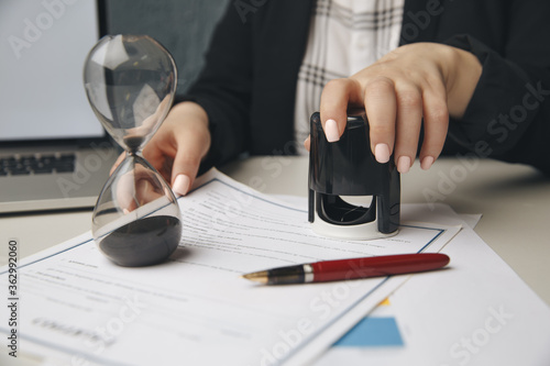 Fotografija Close up on woman's notary public hand stamping the document