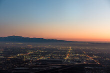 The City Lights Of The Skyline Of The Inland Empire Near Los Angeles California Begin To Appear As The Sun Sets In A Dramatic Orange Sunset. View From Potato Mountain In Claremont Wilderness Park