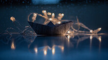 Close-up Of Paper Boat By Illuminated Lighting Equipment
