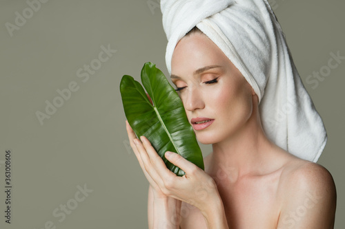 Fotografía A beautiful girl with a towel on her head holds a green leaf in her hands