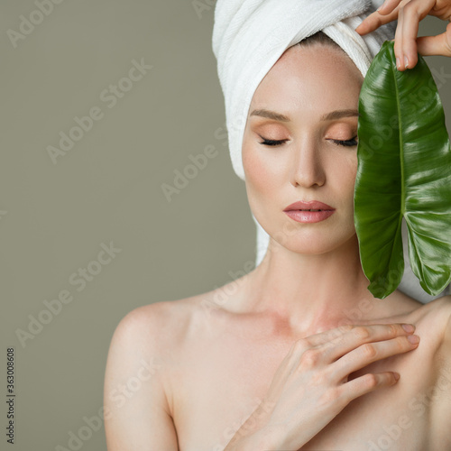 Fotomural A beautiful girl with a towel on her head holds a green leaf in her hands