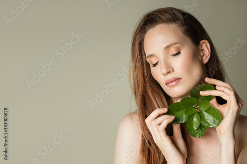 Cuadros en Lienzo A beautiful woman holds a green leaves in her hands