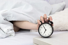 Cropped Hand Holding Alarm Clock While Lying On Bed