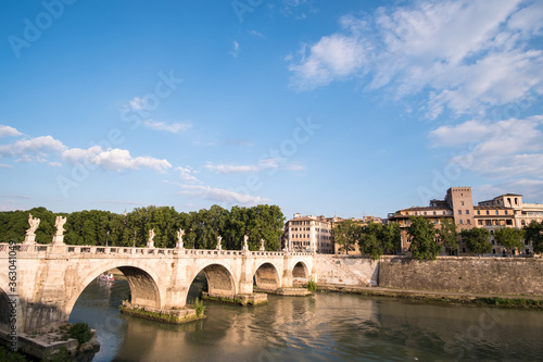 Leinwand Poster Arch Bridge Over River By Buildings Against Sky