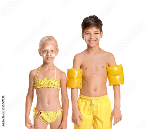 Fototapeta Little children with sun protection cream on their faces against white background obraz
