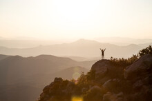 Silhouette Woman With Arm Raised Standing On Mountain Against Sky During Sunset