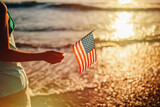Midsection Of Person Holding American Flag Against Sea During Sunset