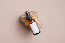 Amber Glass Spray Bottle With White Blank Label On Rock Stone On Beige Background. Natural Organic Cosmetic Product Mockup. Flat Lay, Top View.