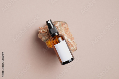 Photo Amber glass spray bottle with white blank label on rock stone on beige background