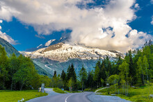 Road By Trees On Snowcapped Mo...