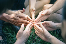 Low Section Of Friends Joining Hands On Grassy Land