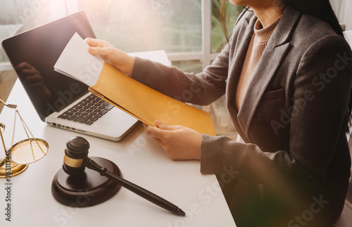 Fototapeta Business and lawyers discussing contract papers with brass scale on desk in office
