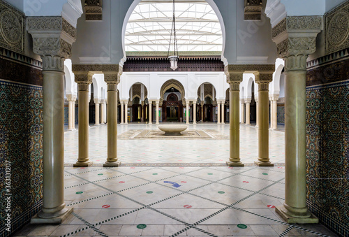 Valokuvatapetti The peristyle of the Great Mosque of Paris, France, borders a tiled courtyard with a circular ablutions basin in the center, covered by a retractable soft roof