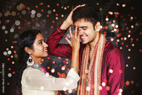 Fototapeta Indian woman is giving blessings to the brother by putting tika on his forehead