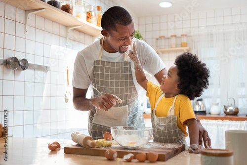 Fototapeta African Father and son enjoying during bake cookies at home together. obraz