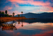 Twilight Reflected In Lake And A Beached Boat