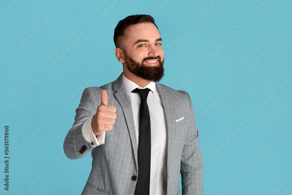 Fototapeta Cheerful millennial businessman showing thumb up gesture on blue background